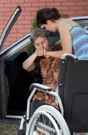 Photo pour Fille aidant femme âgée handicapée sortir de la voiture - image libre de droit
