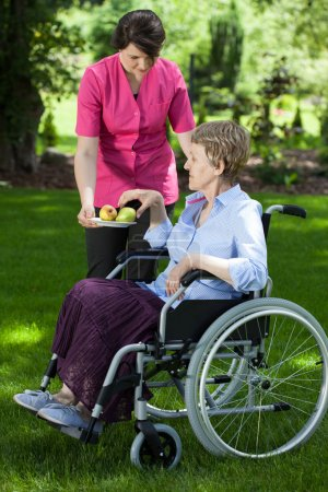 Caregiver giving pear to disabled senior woman
