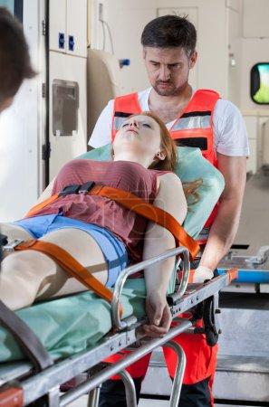 Senseless girl lying on stretcher