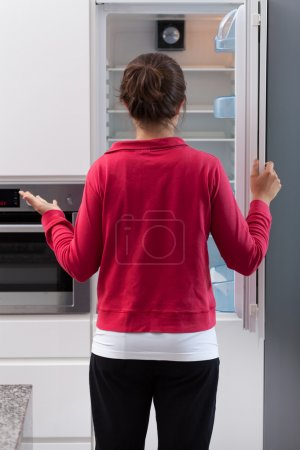 Photo for Girl in tracksuit opening the empty refrigerator - Royalty Free Image