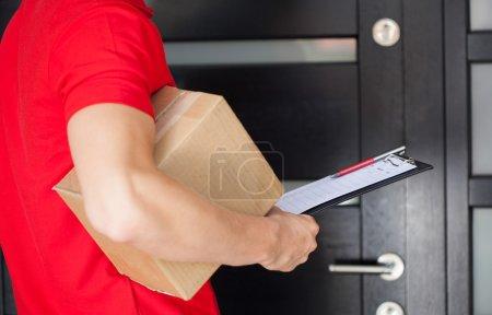 Photo pour Livreur attendre à la porte d'entrée avec un colis - image libre de droit