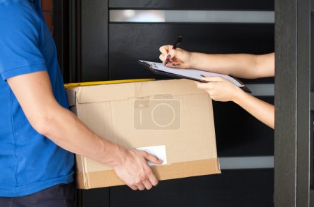 Photo for Delivery guy holding package while woman is signing documents - Royalty Free Image