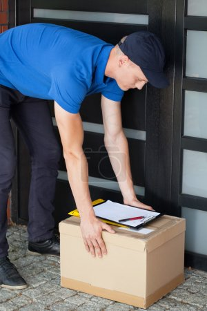 Delivery man putting down parcel