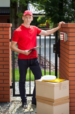 Photo for Delivery man waiting for client with packages - Royalty Free Image