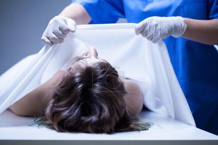 Photo pour Couvrant le corps de la femme dans la morgue, horizontale - image libre de droit