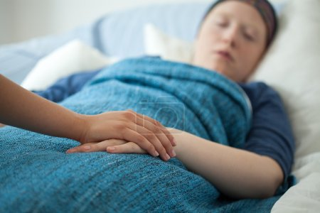 Nurse holding hand of ill woman