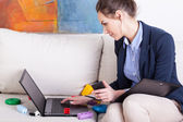 Young mother using laptop to work at home