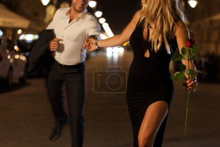 An elegant couple holding hands when running on a ...