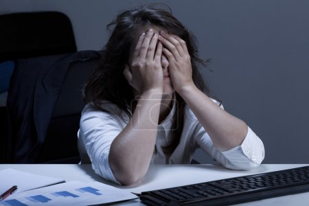 Photo for Frustrated young businesswoman analyzing chart during overtime - Royalty Free Image