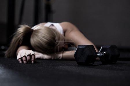 Photo pour Épuisé de jeunes fille couchée sur un plancher après la formation - image libre de droit
