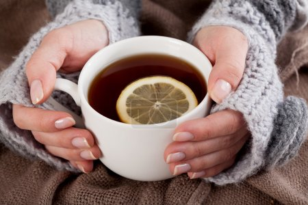 Photo for Woman's hand holding cup of tea with lemon on a cold day - Royalty Free Image