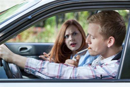 Photo pour Femme en colère contre l'homme pour cigarette fumer en voiture - image libre de droit