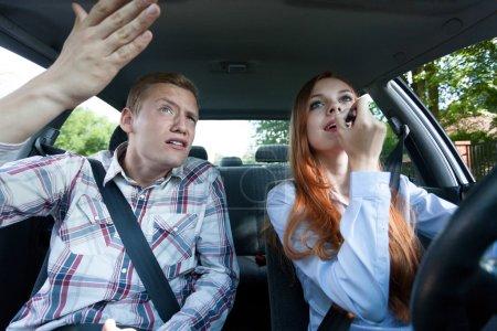Photo pour Jeune homme en colère contre la femme pour mettre le rouge à lèvres en voiture - image libre de droit