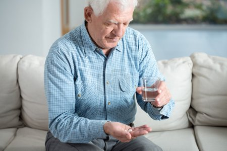 Photo for Ill senior man taking pill and drinking water - Royalty Free Image