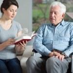 Senior care assistant reading book elderly man...