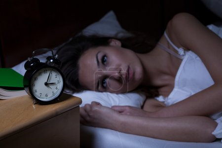 Photo for Woman with insomnia lying in bed with open eyes - Royalty Free Image