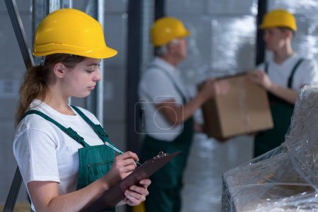 Female manufacturing labourer holding clipboard