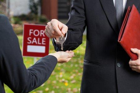 Photo pour Agent immobilier donnant les clés à l'acheteur - image libre de droit
