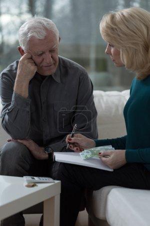 Photo pour Vieux mari inquiété parlant avec sa femme au sujet du budget - image libre de droit