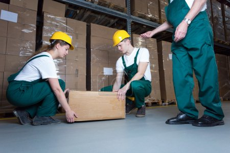 Photo pour Deux jeunes travailleurs soulevant une lourde boîte dans un entrepôt - image libre de droit