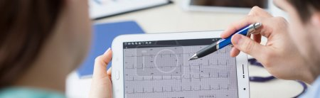 Modern cardiologists analyzing electrocardiogram