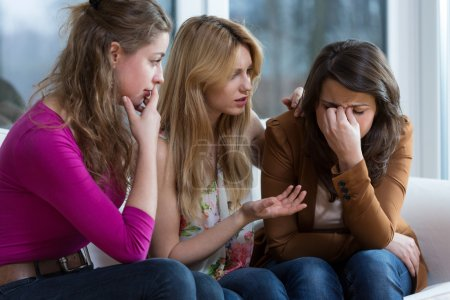 Photo for Two young worried girls supporting crying friend - Royalty Free Image