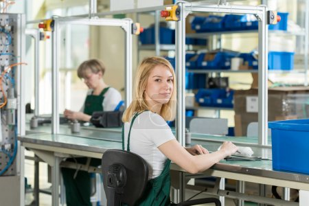 Beauty young woman working on production line...