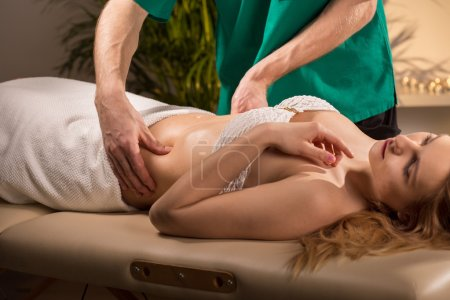 Woman having done abdominal massage