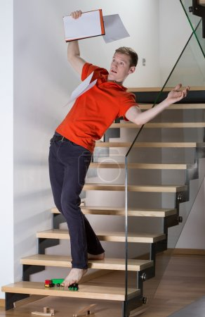 Man stepping on toys on stairs