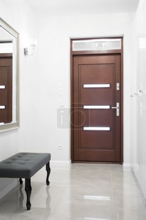 Photo of wooden entrance door in big white hallway...