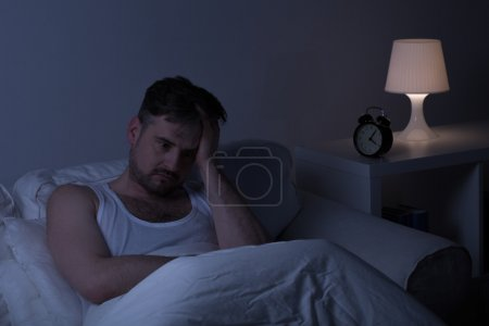 Photo for Man suffering from sleeplessness sitting in the bed - Royalty Free Image