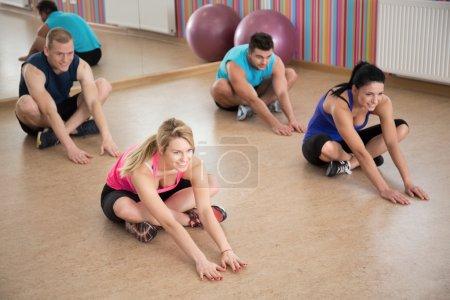 Photo pour Des sportifs pendant les étirements dans un club de fitness - image libre de droit