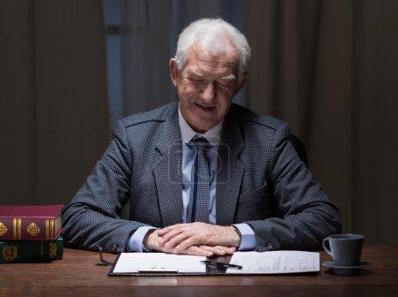 Photo pour Homme d'affaires élégant plus âgé s'asseyant dans le bureau avec la paperasse - image libre de droit