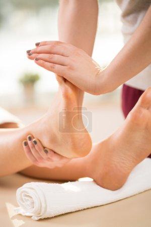 Photo pour Femme thérapeute qui s'étend des pieds de la jeune femme - image libre de droit