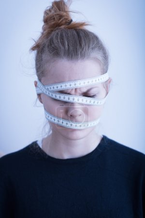 Photo for Measuring tape wrapped around the female head - Royalty Free Image