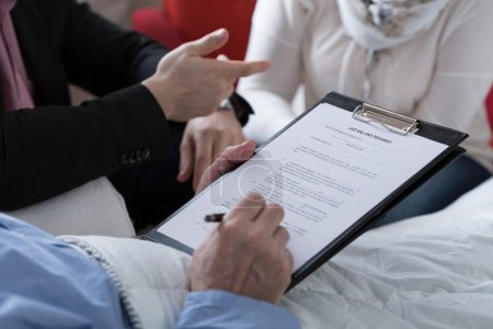 Close-up of older sick man holding his last will a...