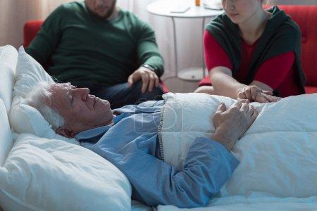 Photo pour Enfants adultes disant au revoir avec le père mourant âgé à l'hôpital - image libre de droit