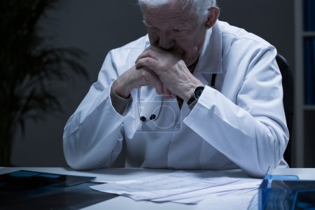 Photo for Old doctor with deep depression crying in solitude - Royalty Free Image