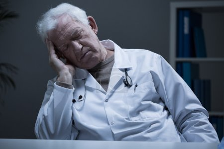 Photo for Mature tired man physician sleeping at work in office - Royalty Free Image