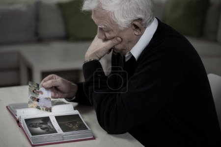 Widower looking at the photos and remembering dece...