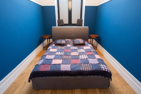 Double bed with colorful overlay in small bedroom...