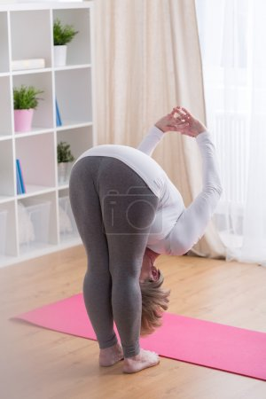 Lady doing bending pose in yoga