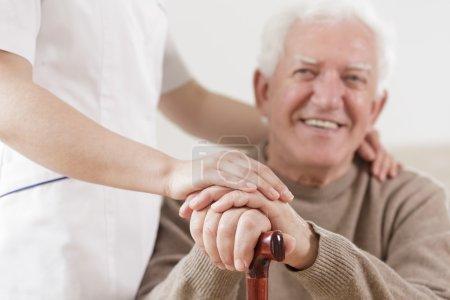 Photo pour Homme senior souriant et aidant infirmière utile - image libre de droit
