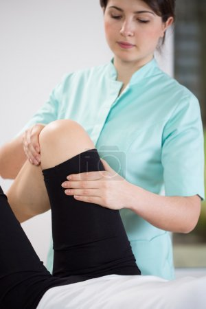 physiotherapist flexing patient's knee
