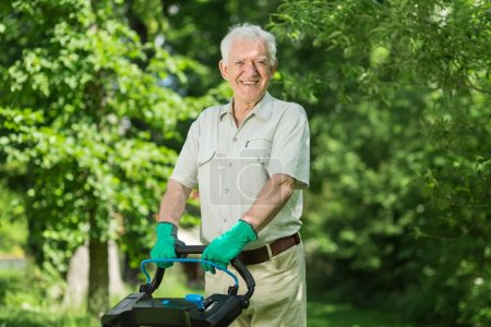 Elderly man mows a lawn