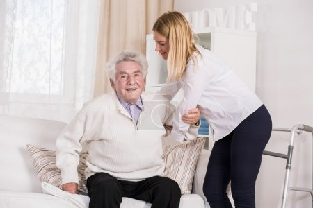 Photo pour Jeune assistante soignante aidant un homme âgé - image libre de droit