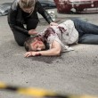 Dead man after car crash and prostrate driver...