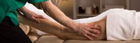 Photo for Close-up to man's hands massaging woman's thigh - Royalty Free Image