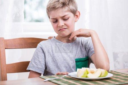 Boy refusing to eat apple
