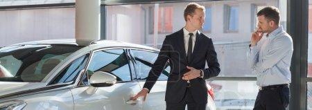 Photo pour Concessionnaire automobile, vente voiture de luxe moderne à un client - image libre de droit